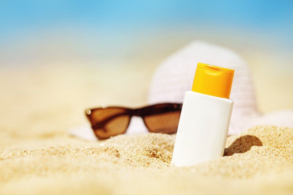 Healthy skincare products on the beach: sunglasses, a beach hat, and sunscreen.