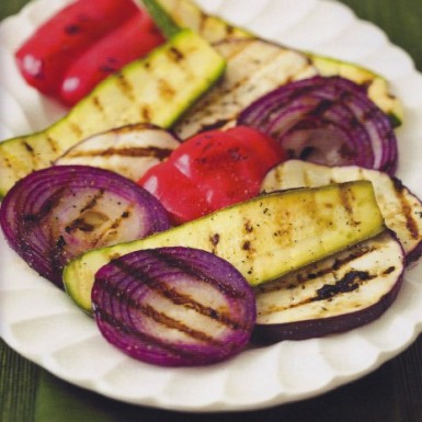 a white plate filled with grilled, onion, zucchini. and peppers