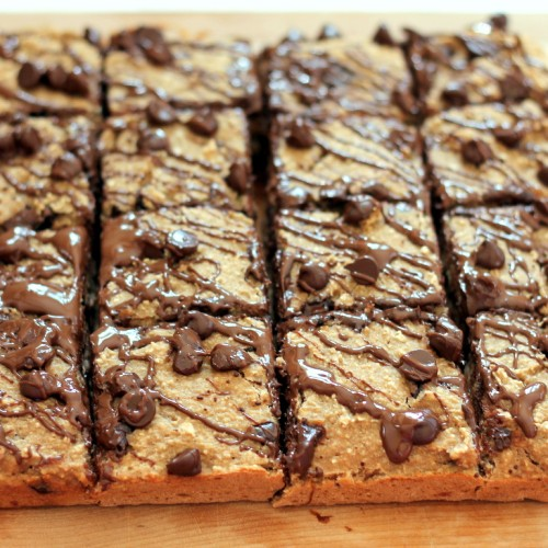 Healthy Banana Bread Chocolate Chip Oat Breakfast Bars drizzled with chocolate on a wooden table