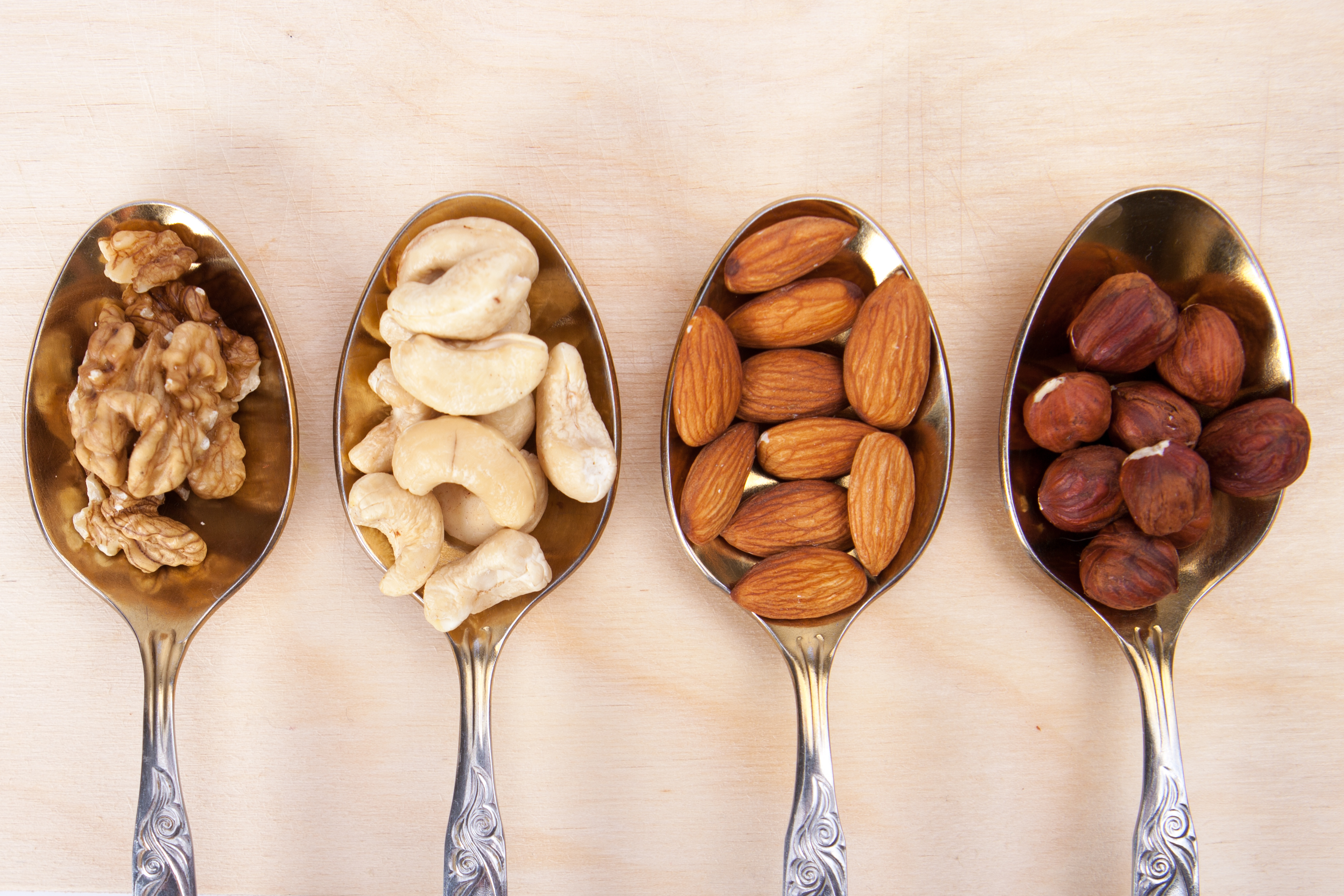 Almonds, cashews, hazlenuts and walnuts on spoons for a healthy snack.