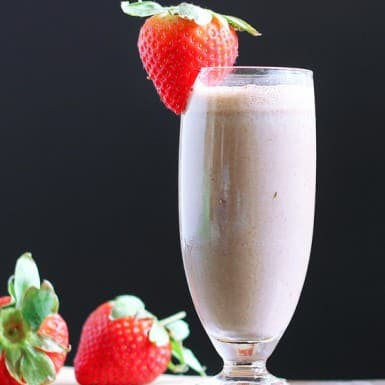 A Chocolate Silk Smoothie in an old-fashioned glass with a strawberry on the rim.