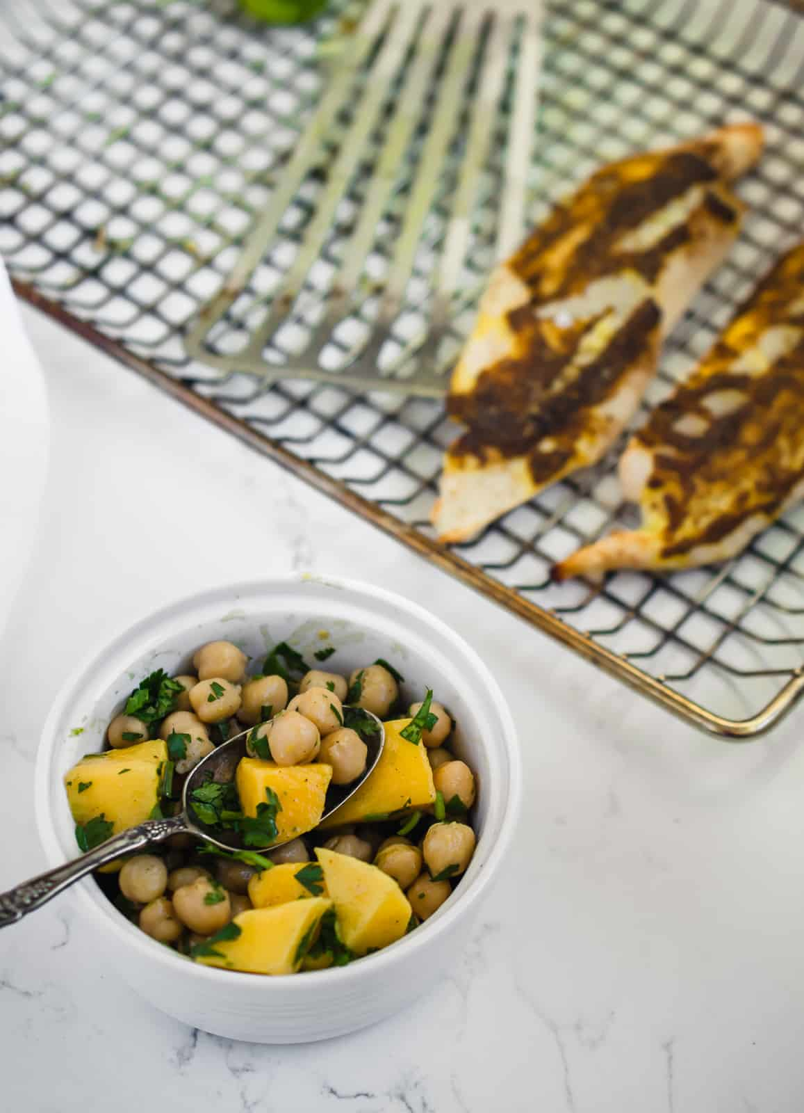 Bowls of mango chickpea salsa with grilled tilapia on grill pan