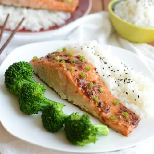a white plate with a seasoned salmon filet topped with a glaze and side of broccoli and rice