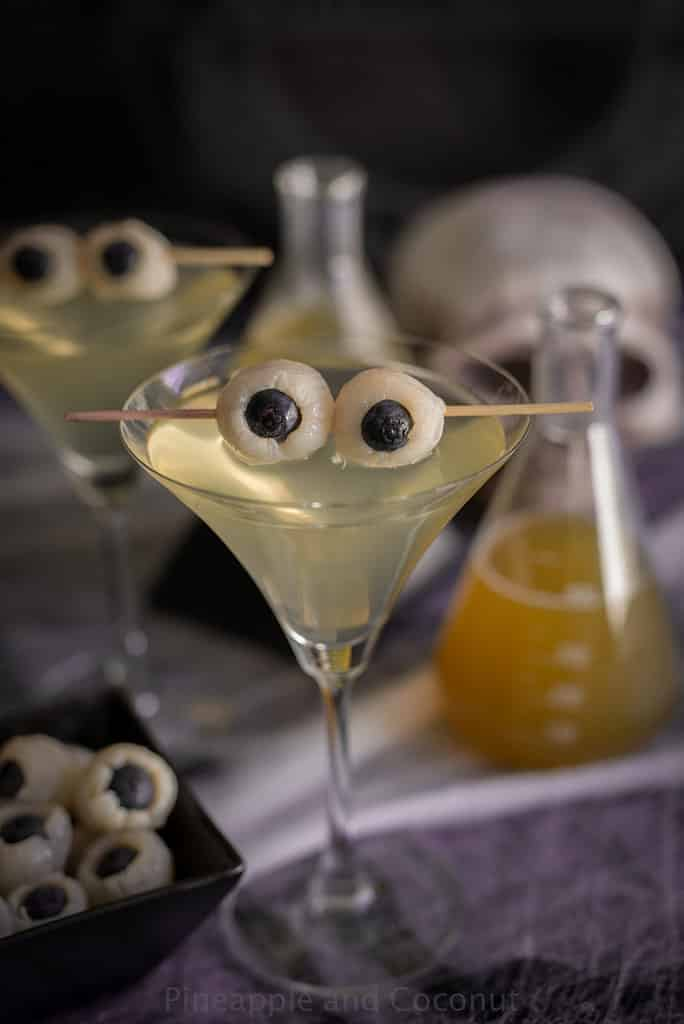 A Creepy Eyeball Martini on a table with a flask and viles to make it look spooky for Halloween.