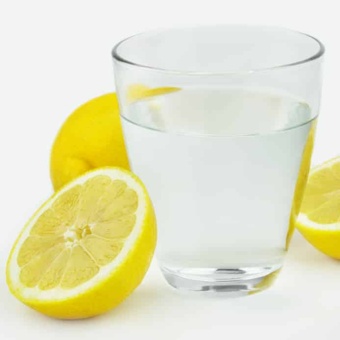 A glass of lemon water with lemons around it