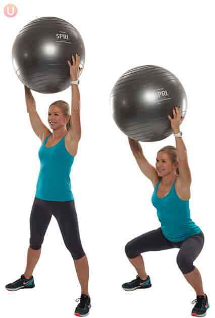 Chris Freytag demonstrating a squat holding a stability ball wearing black yoga pants and a blue top