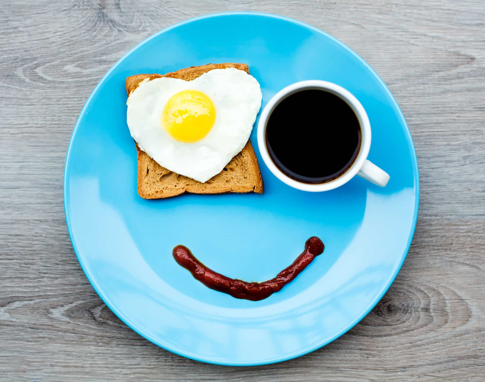 A blue plate with a piece of toast, egg, and coffee.