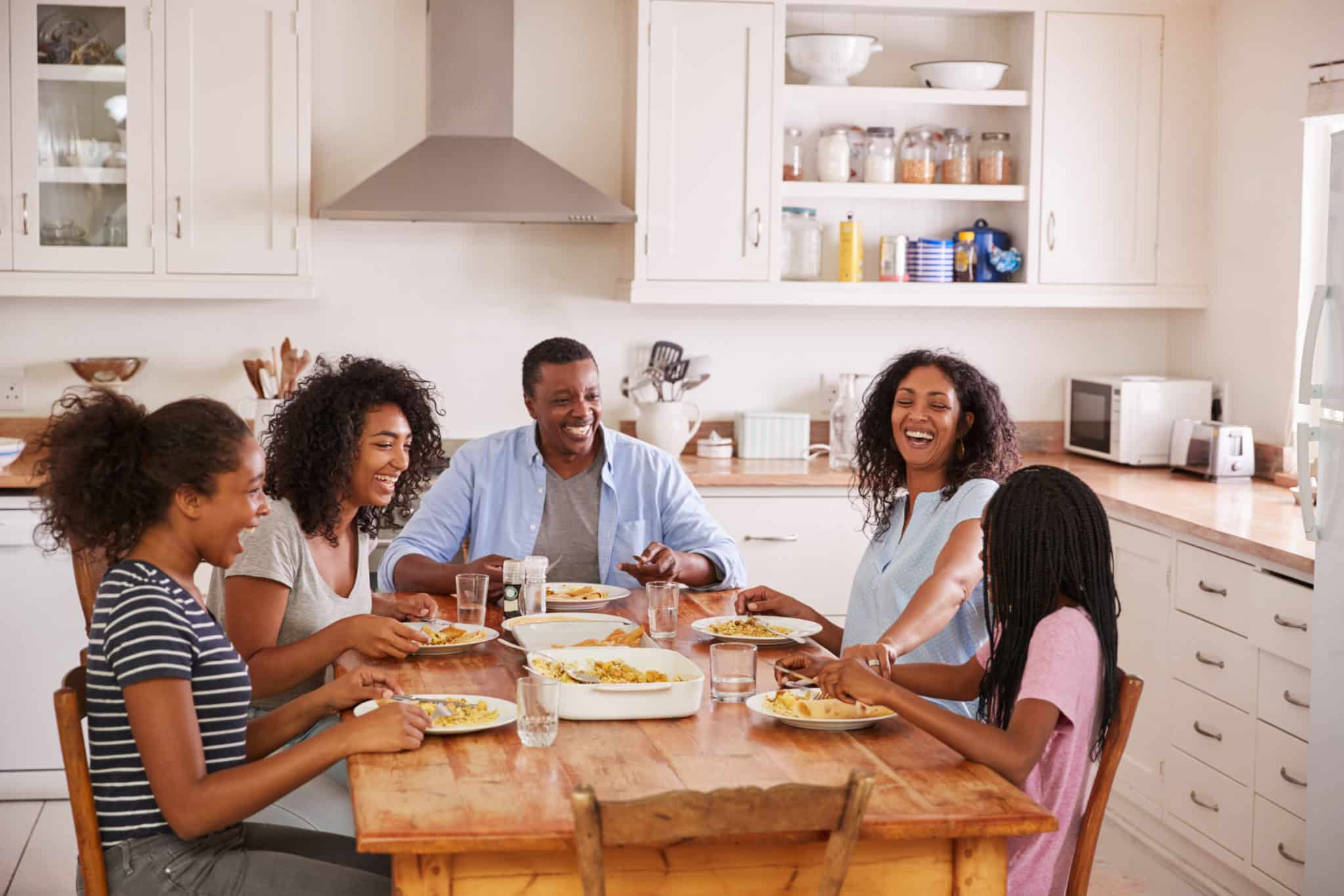 Family sitting at kitchen table smiling and talking