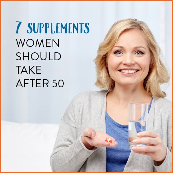 Woman over 50 taking vitamins with glass of water