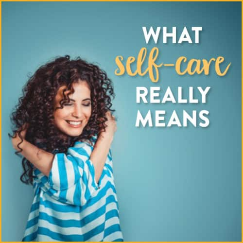 Woman with curly hair wrapping arms around herself with text: what self-care really means