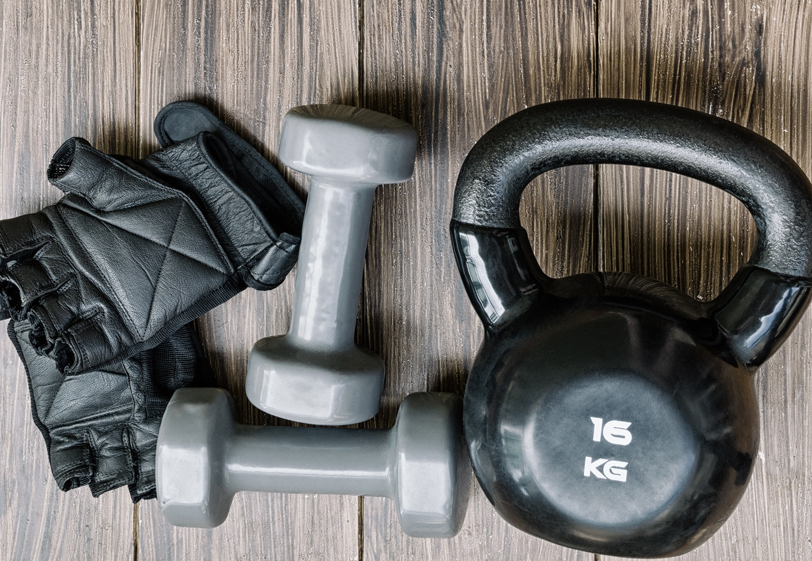 Gray dumbbells and black kettlebell with workout gloves on wood background