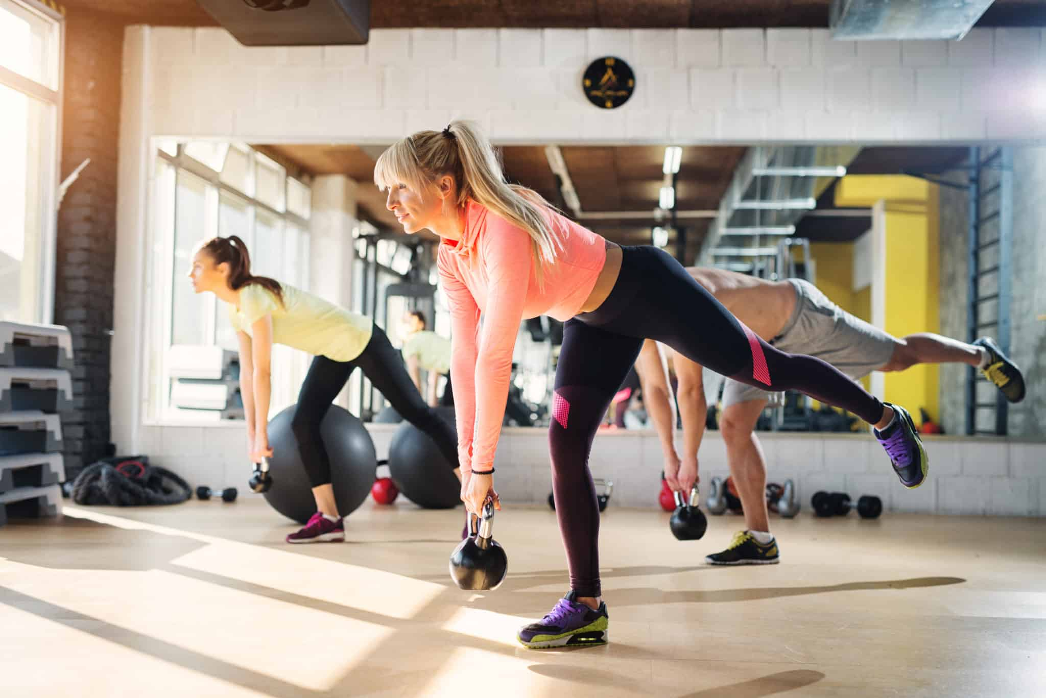 Woman using kettlebells in group fitness class