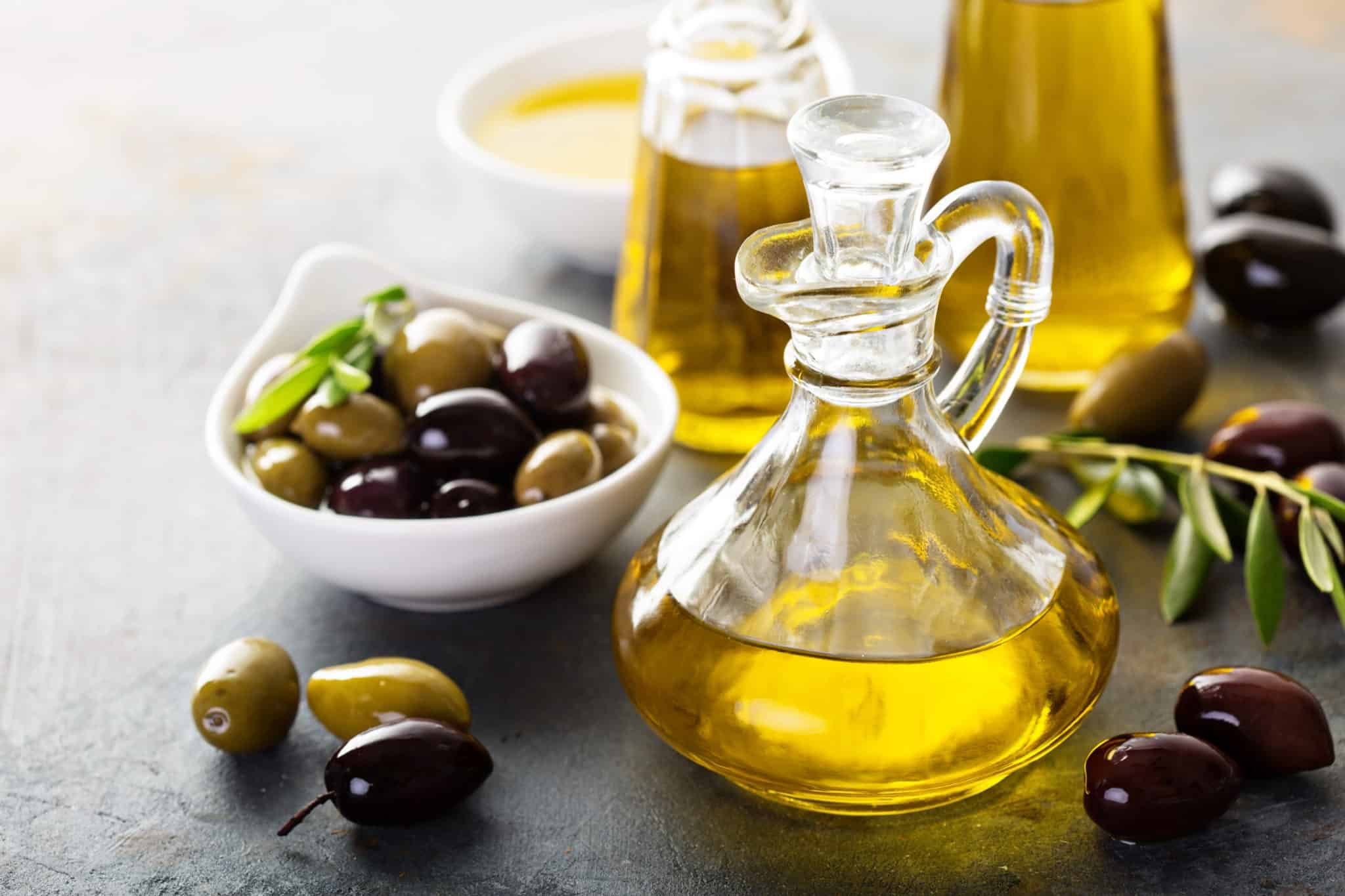 Olive oil in bottle with olives in bowl