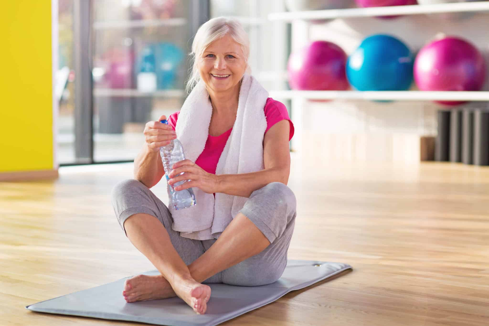 Senior woman sitting on yoga mat with towel around neck and holding water bottle in exercise studio