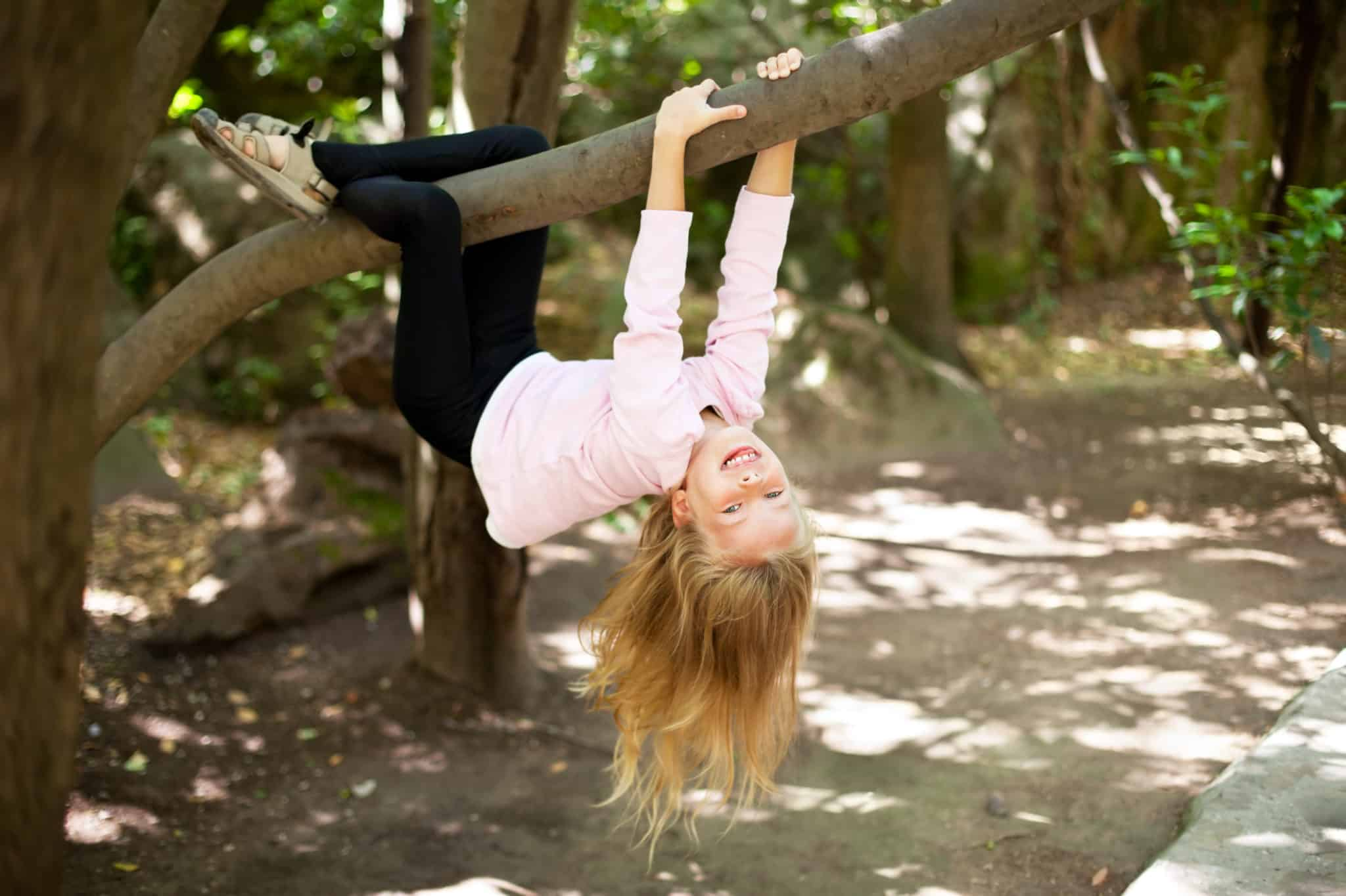 Little girl hanging from a tree branch smiling